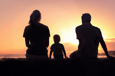 Silhouette of a young mum, son and dad watching the sunset