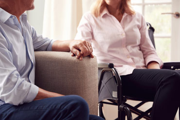 Wife sitting in a wheelchair holding her husbands hand